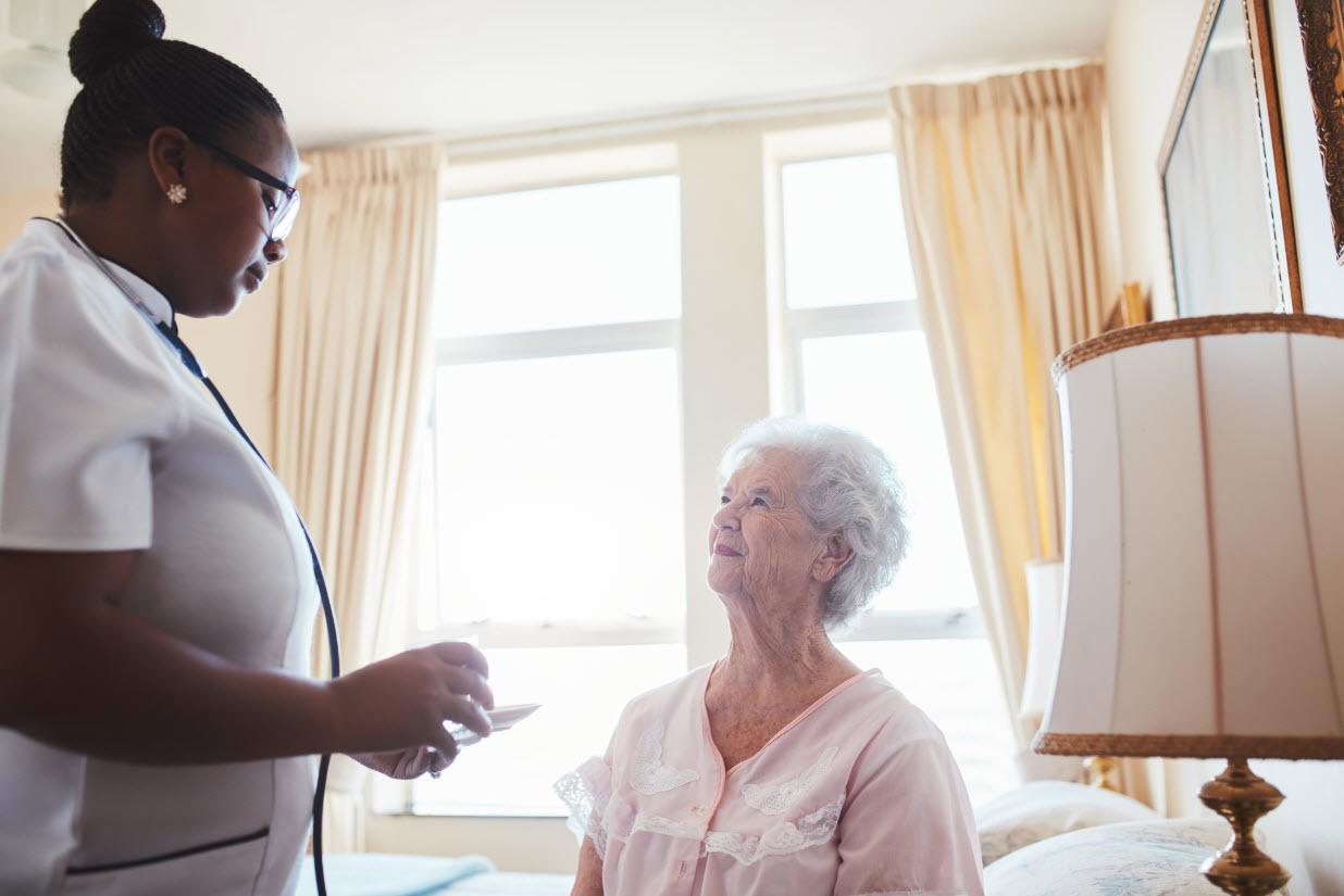 female-nurse-assists-an-elderly-female-patient-wit-P68YX2Dweb