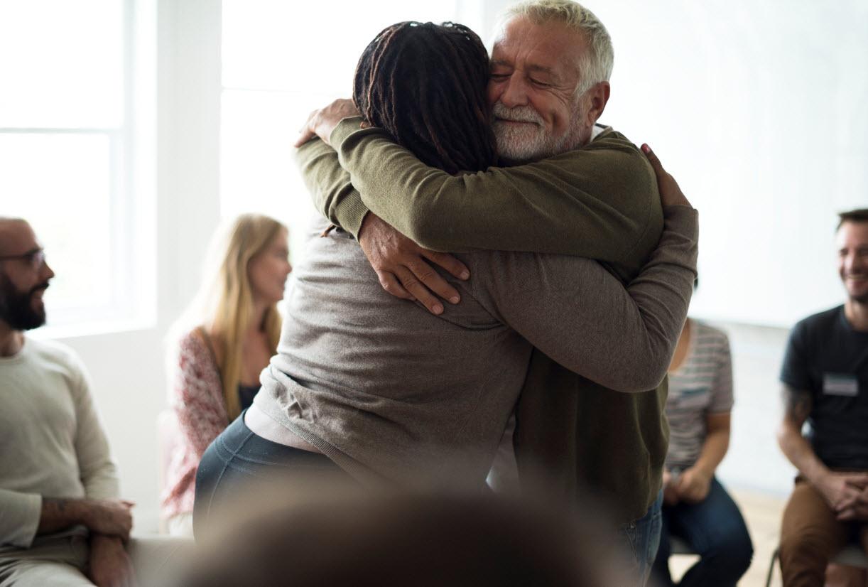 senior-man-hugging-woman-in-support-group-8AWMB9Mweb